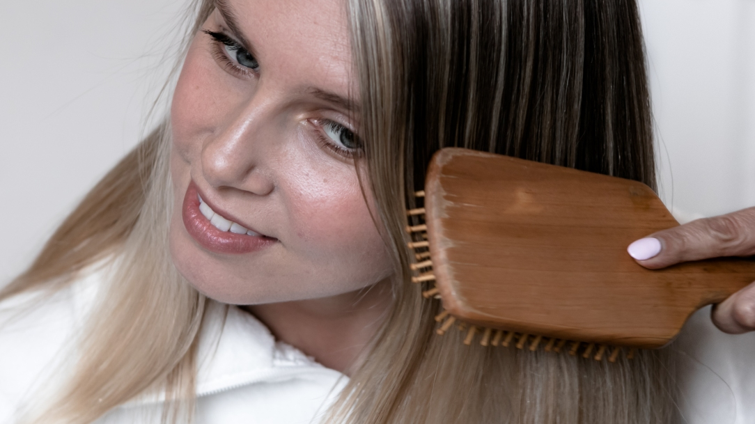 blonde girl brushing hair, hair care products, summer hair care tips, tame frizzy hair, all natural products